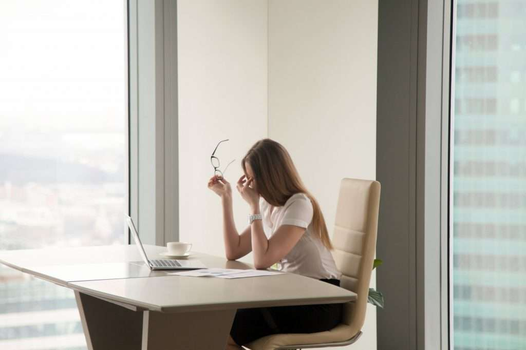 Exhausted businesswoman sitting at office